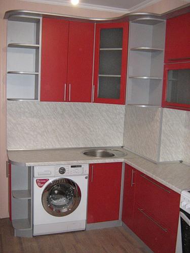 111 Маленькая угловая кухня в красном цвете. В кухне расположена стиральная машинка под столешницей