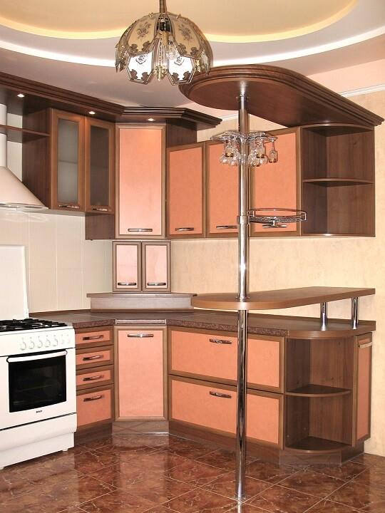 127 Небольшая угловая кухня с барной стойкой,корпус ДСП,фасады МДФ пленочный,рамочный. Теплое сочетание персикового цвета фасадов и орех  корпуса создаю уют и тепло на кухне ,а выполненый в классическом стиле карниз с подсветкой подчеркнул стиль кухни