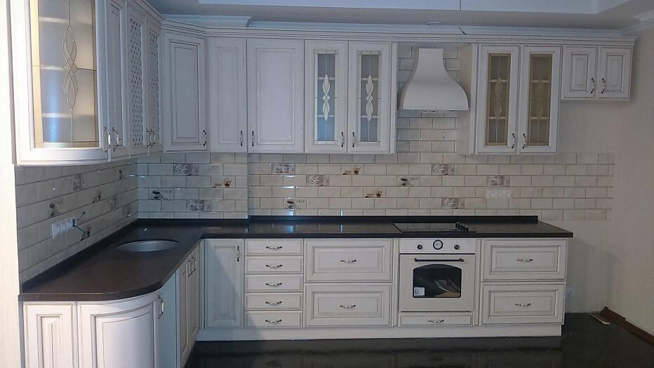 141 L-образная угловая кухня, корпус ДСП,фасады дерево,каменная столешница,стиль кухни классика.Дизайн мебели разработан для кухни студио,что позволило гармонично объединить кухню и гостинную комнату,неординарное сочетание светлой кухни ,темной столешницы,темного пола и потолка визуально увеличило площадь помещения и акцентировало красоту классики